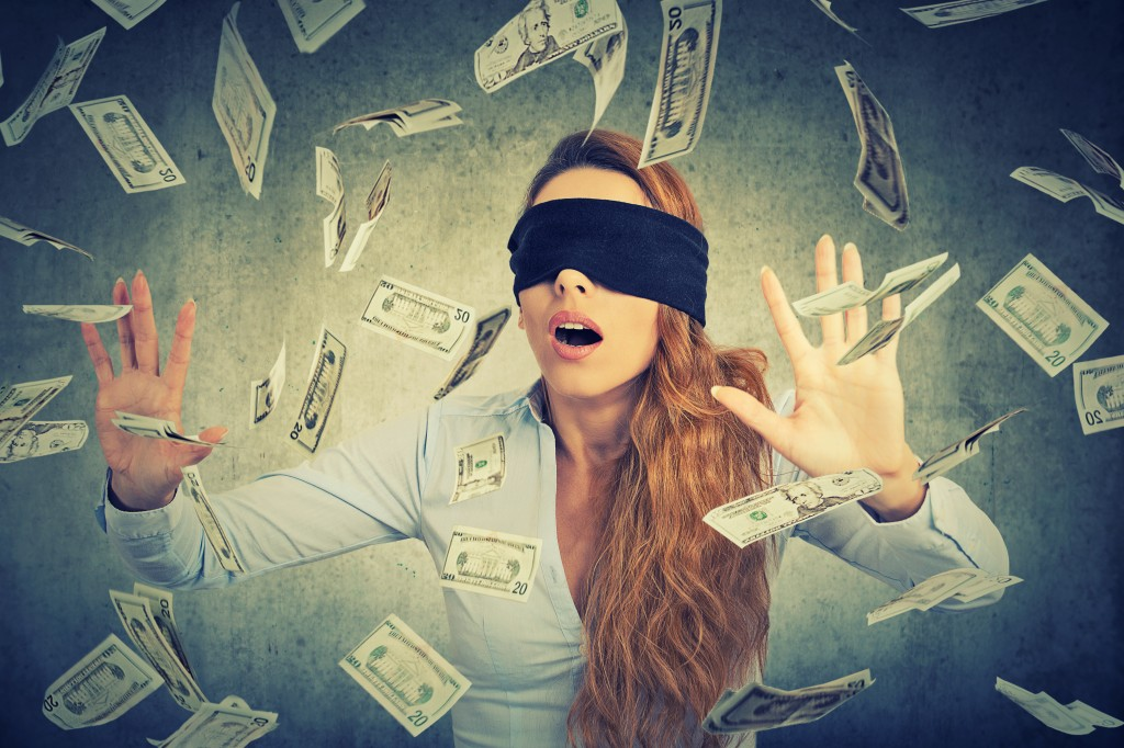 Blindfolded young entrepreneur  businesswoman trying to catch dollar bills
